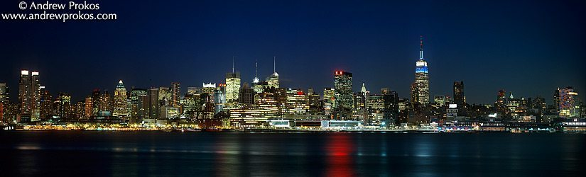 A panoramic skyline of Midtown Manhattan, the Hudson River and the Empire State Building at night as seen from Hoboken, NJ