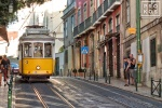 A street scene photo of a classic street trolley in the Alfama district of Lisbon, Portugal