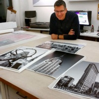 Photographer Andrew Prokos signing black and white fine art prints of New York landmark buildings