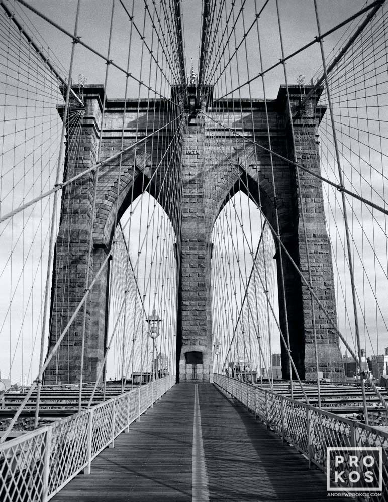 A black and white photograph of the tower and suspension cables of the Brooklyn Bridge, New York City.