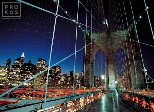 A color cityscape photo of the tower and suspension cables of the Brooklyn Bridge at night, New York City