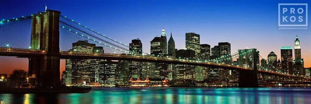 A panoramic skyline of the Brooklyn Bridge and Lower Manhattan at dusk, New York City.