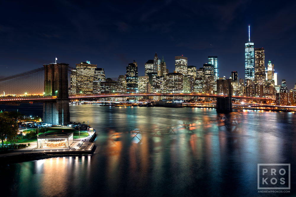 A wide angle view of the entire span of the Brooklyn Bridge, East River, and Lower Manhattan skyline at night.