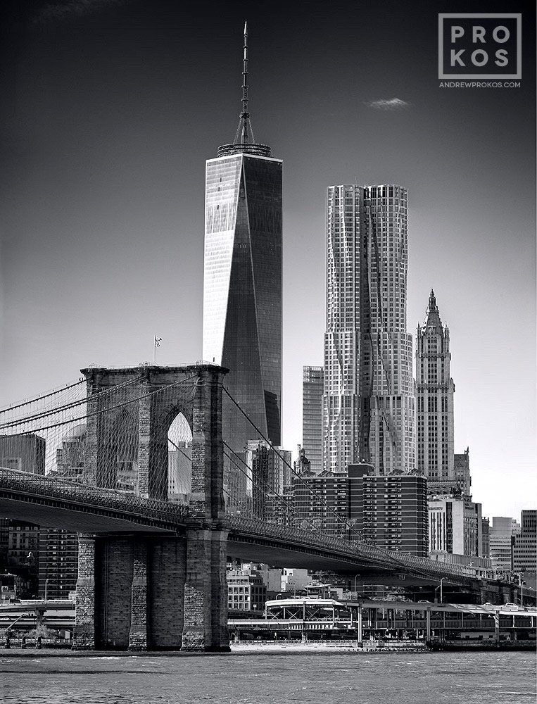 A daytime view of the Brooklyn Bridge and the skyscrapers of Lower Manhattan, including;
