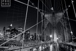 A black and white long-exposure photo of the suspension cables of the Brooklyn Bridge at night, New York City