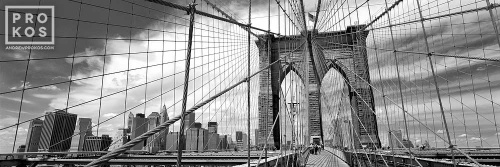 A black and white panoramic photo of the Brooklyn Bridge and its famous suspension cables, New York City