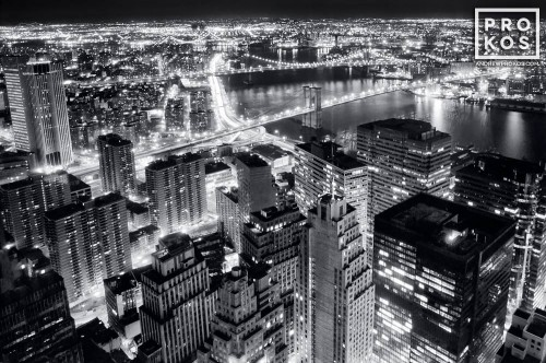 A black and white aerial view of Lower Manhattan and the Brooklyn Bridge at night, New York City