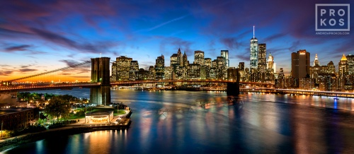 A panoramic view of the Brooklyn Bridge and the Lower Manhattan skyline at dusk, New York City
