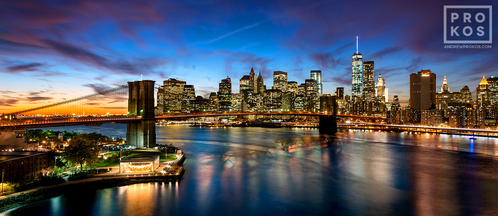 "A panoramic photo of the Brooklyn Bridge and the Lower Manhattan skyline at dusk, New York City. Framed fine art prints of this photo are available up to 72"" wide."