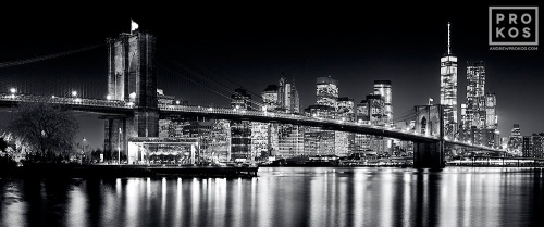 A panoramic photo of the Brooklyn Bridge and Lower Manhattan at Night in black and white. Framed fine art prints and high-resolution images available.