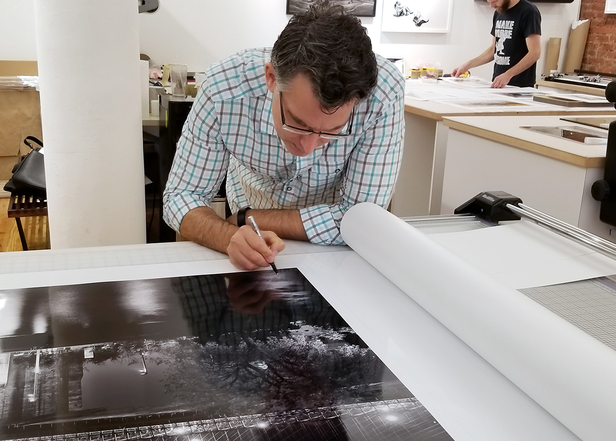 "Andrew Prokos signing a 90"" limited edition print of ""Panoramic Skyline of Brooklyn Bridge and Lower Manhattan at Night"""