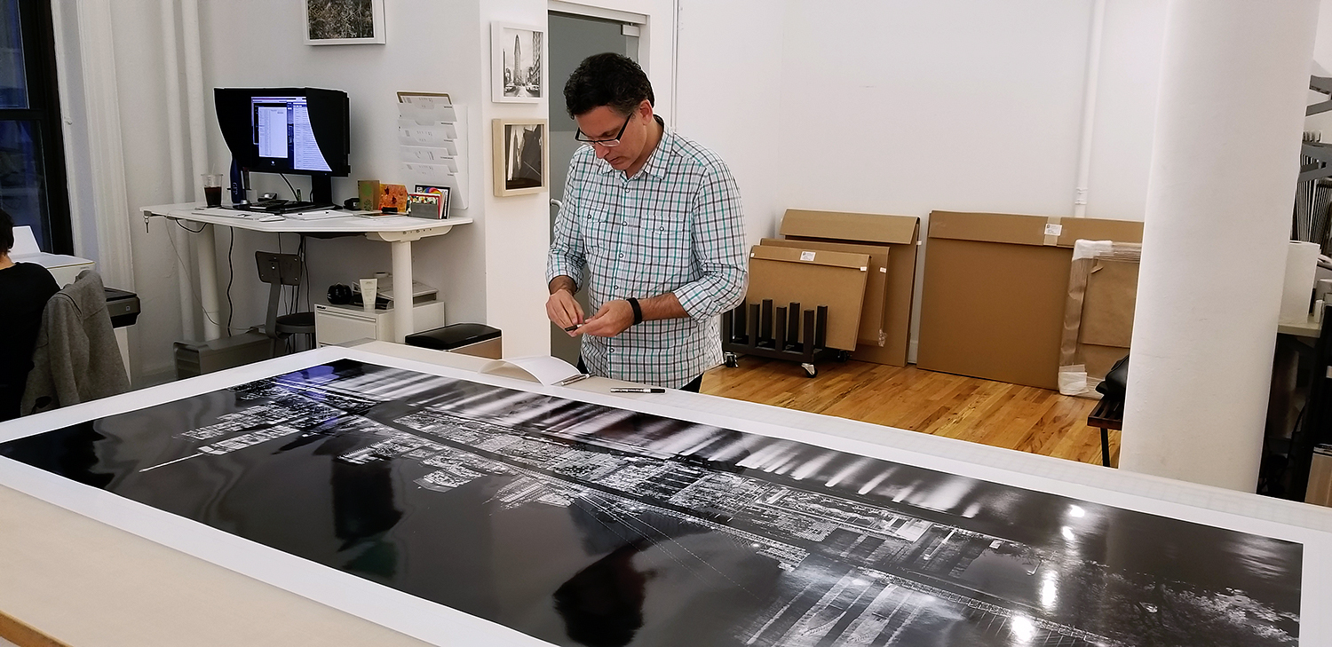 "Andrew Prokos with his 90"" limited edition print of ""Panoramic Skyline of Brooklyn Bridge and Lower Manhattan at Night"""