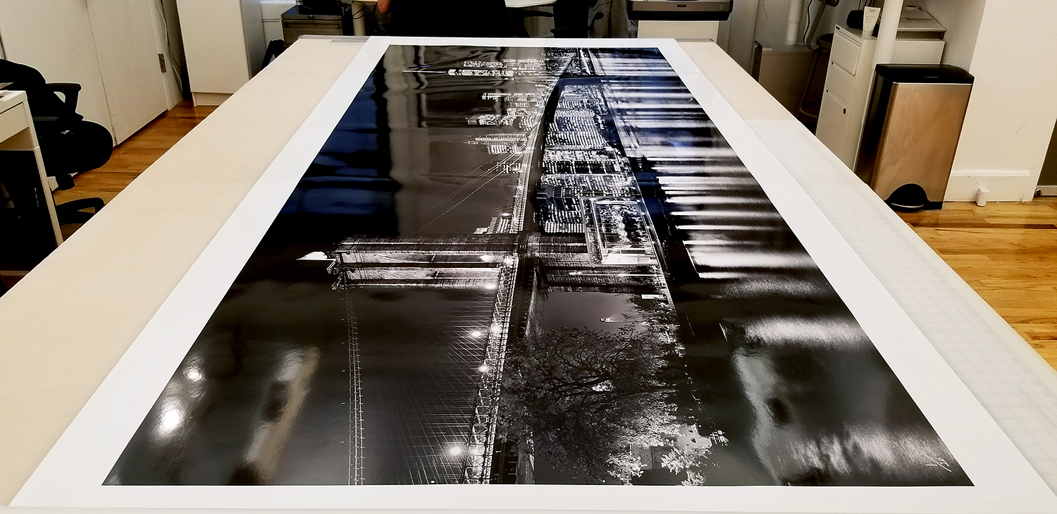 "A 90 inch limited edition print of ""Panoramic Skyline of Brooklyn Bridge and Lower Manhattan at Night"" by photographer Andrew Prokos"