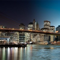 An ultra-high-definition panoramic skyline photo of the Brooklyn Bridge and Manhattan transitioning from day to night, from Andrew's 'Night & Day' series.
