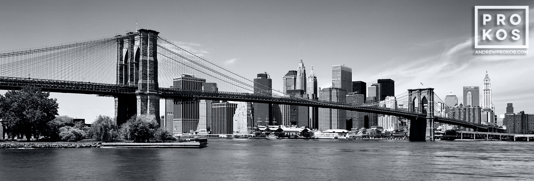 A panoramic skyline of the Brooklyn Bridge and Lower Manhattan in black and white, New York City