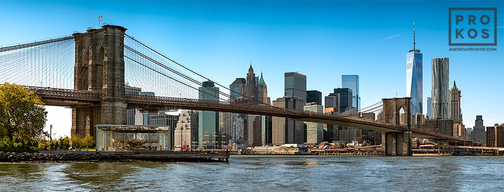 A panoramic photograph of the Brooklyn Bridge and Lower Manhattan skyline during the day, New York City.