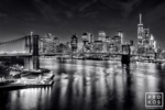 A long-exposure night view of the Brooklyn Bridge, East River, and Lower Manhattan skyline in black and white. Available as limited edition fine art prints framed in various styles.