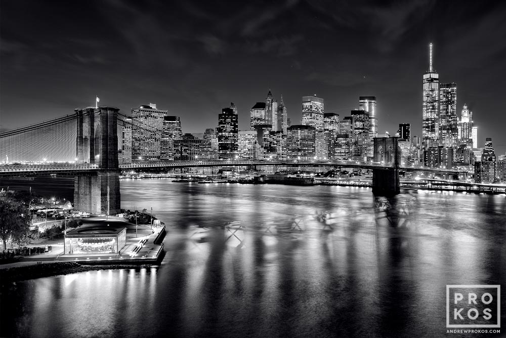 A photograph of the Brooklyn Bridge, East River, and Lower Manhattan skyline at night in black and white.