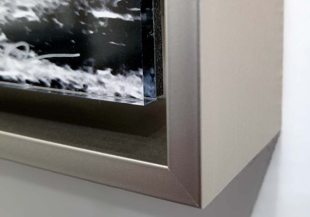 A detail of our acrylic float mount with brushed aluminum float frame