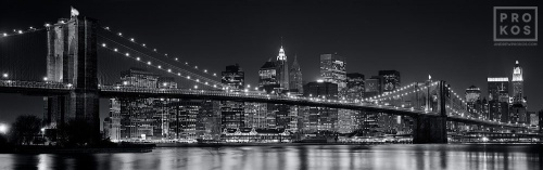 A panoramic skyline of the Brooklyn Bridge and Lower Manhattan at night in black and white
