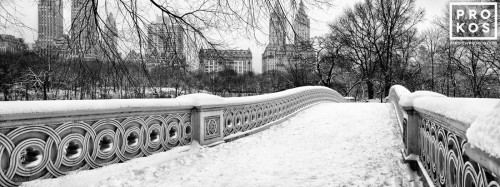 A black and white panoramic landscape photo of Central Park's Bow Bridge in Winter, New York City