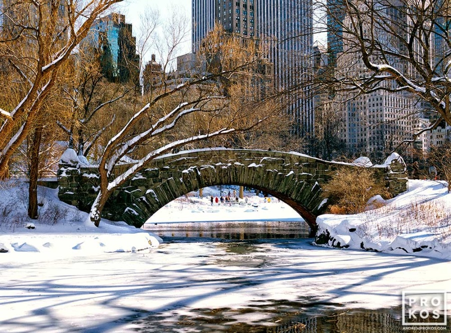 A color landscape photo of Central Park's Gapstow Bridge spaning a frozen Pond in Winter, New York City