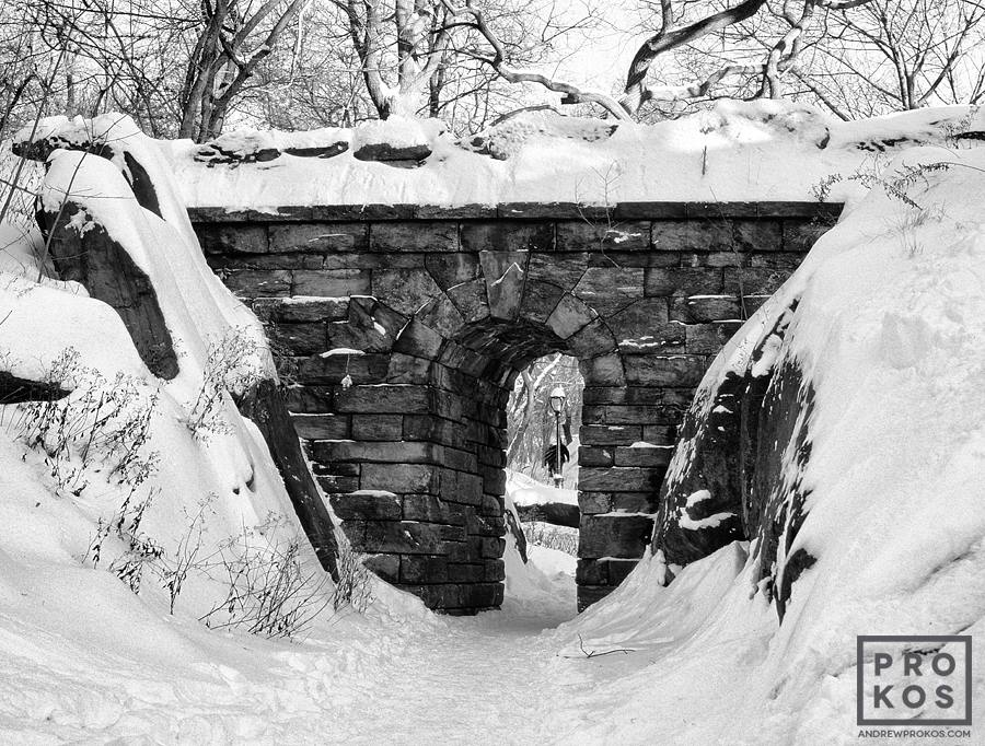 A black and white landscape photo of Central Park's Rustic Stone Arch under a blanket of Winter snow, New York City