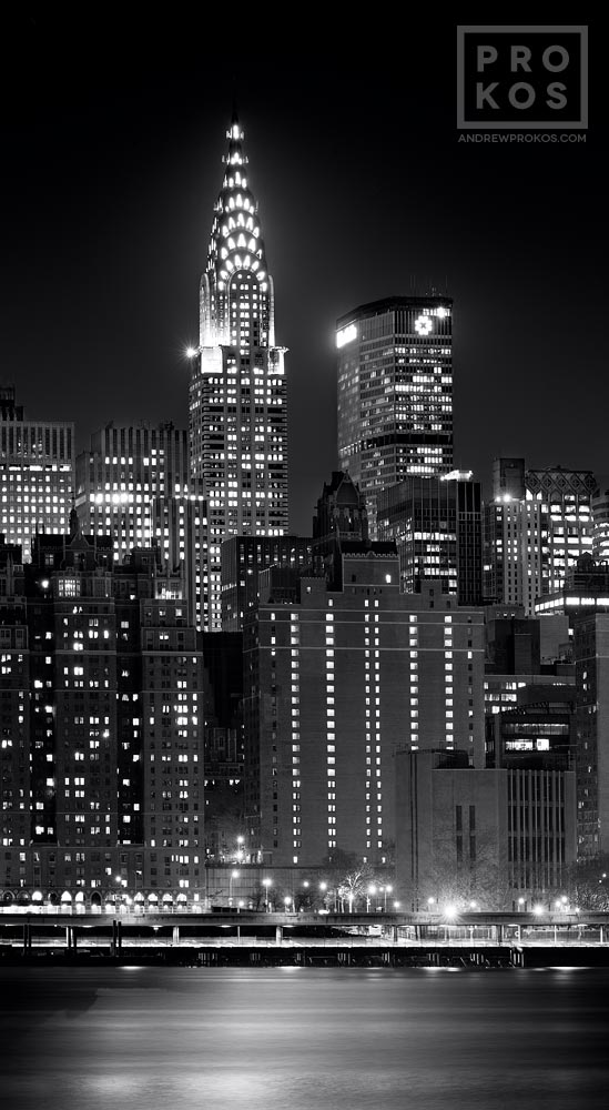 A panoramic view of Midtown Manhattan and the Chrysler Building at night in black and white.