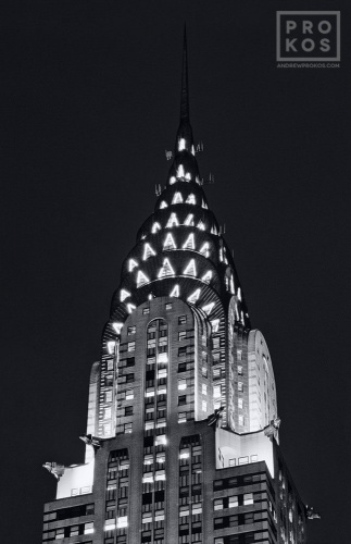 A black and white fine art architectural photo of the illuminated spire of the Chrysler Building at night