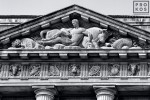 A black and white architectural detail photo of the pediment from the US Department of Commerce building in black and white, Washington DC