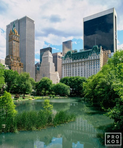 A color landscape photo of the Plaza Hotel and Fifth Avenue skyline as seen from the Pond in Central Park, New York City
