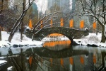 A panoramic landscape photo of Gapstow Bridge and the Lake in Central Park in winter