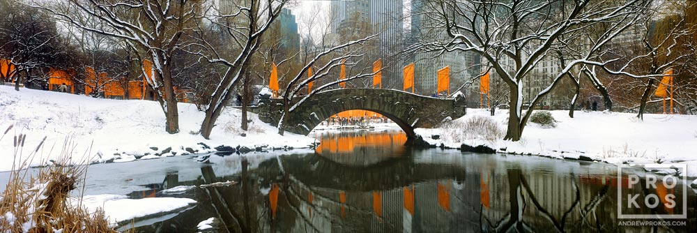 A panoramic landscape photo of Gapstow Bridge and the Lake in Central Park in winter. High-definition fine art prints of this photo are available up to 120 inches wide.