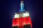 An architectural photo of the Empire State Building at night, with lights in red, white, and blue, New York City