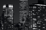 A vertical panoramic view of the Empire State Building at night in black and white, New York City