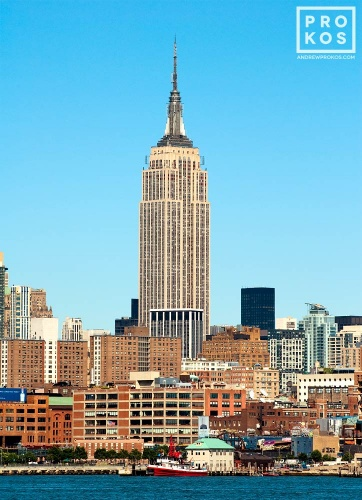A color cityscape photo of the Empire State Building as seen from Hoboken, New Jersey during the day