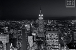 A black and white cityscape photo of the Empire State Building and Midtown Manhattan at night as seen from Rockefeller Center