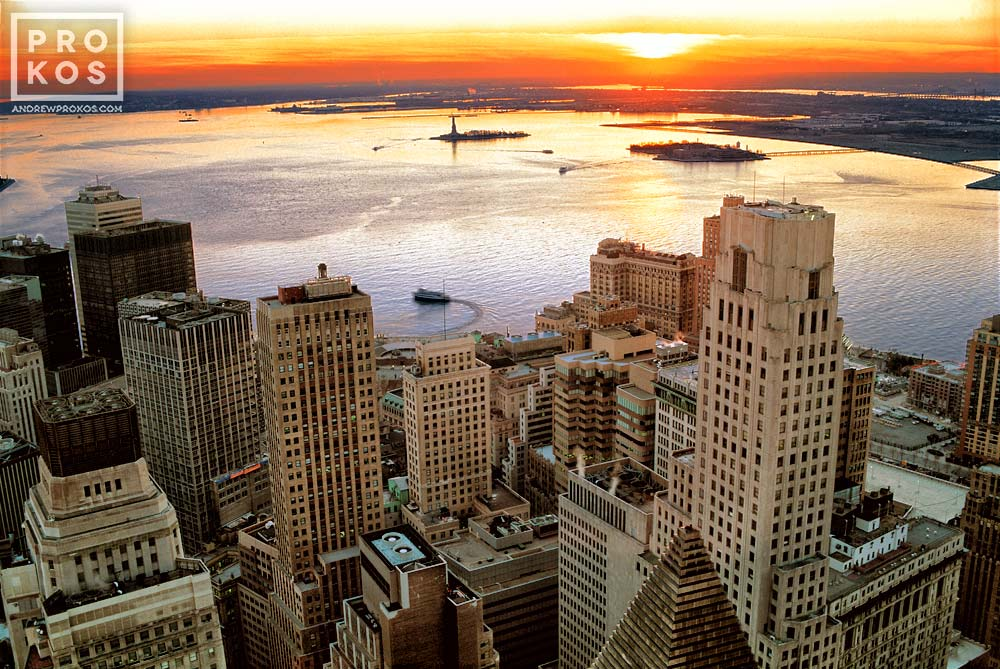 An aerial view of the skyscrapers of Lower Manhattan and New York Harbor at sunset