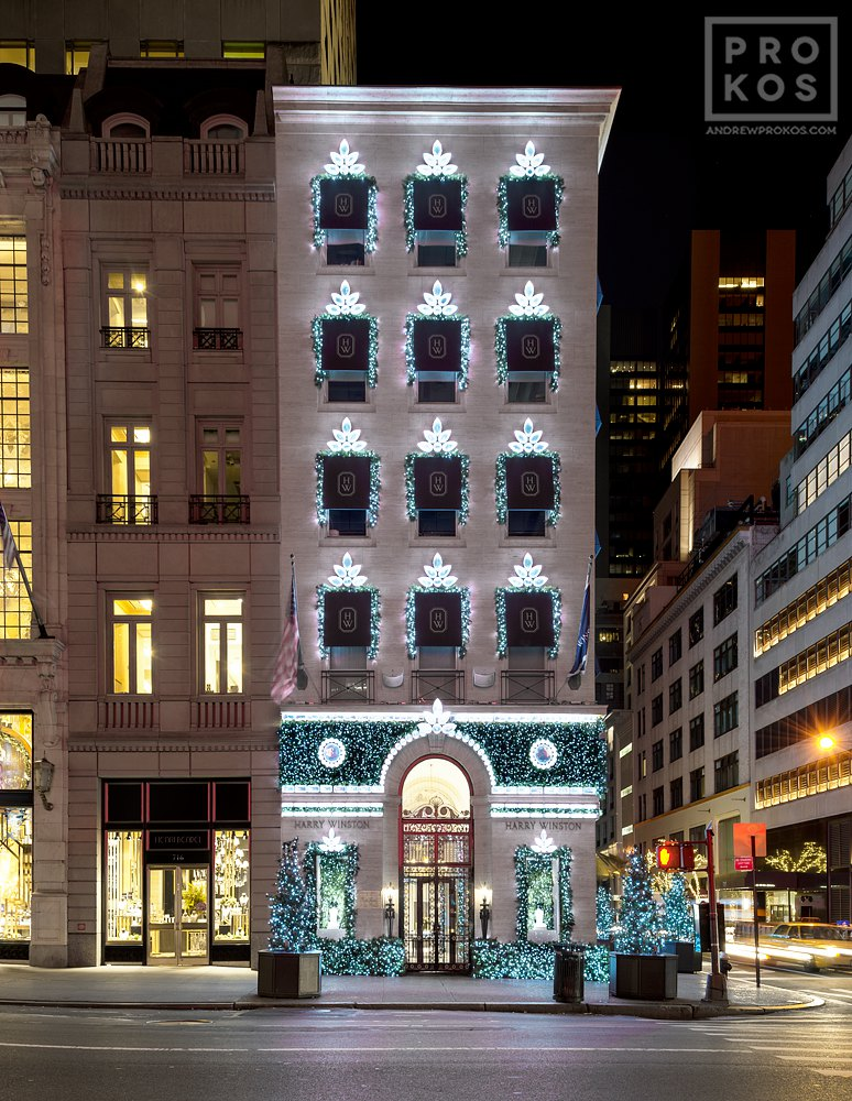 A photo of the decorated facade of Harry Winston Jewelers on New York's Fifth Avenue at night during Christmas.