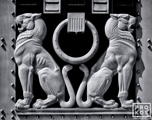 A black and white architectural detail photo of two lions from the doors of the US Justice Department in Washington DC