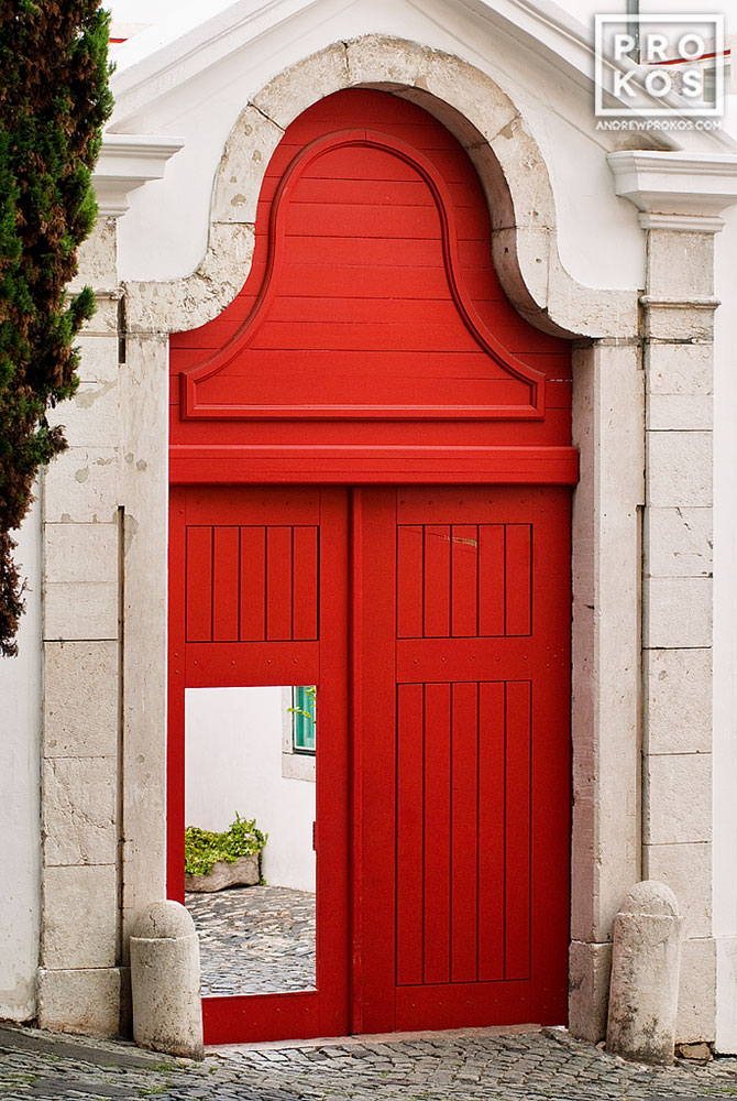 A fine art photo of a bright red door leading to a whitewashed courtyard in the Alfama neighborhood of Lisbon, Portugal