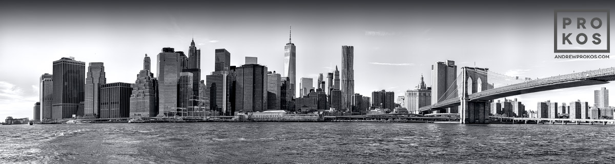 A black and white panoramic photograph of the Lower Manhattan skyline and the Brooklyn Bridge, New York.