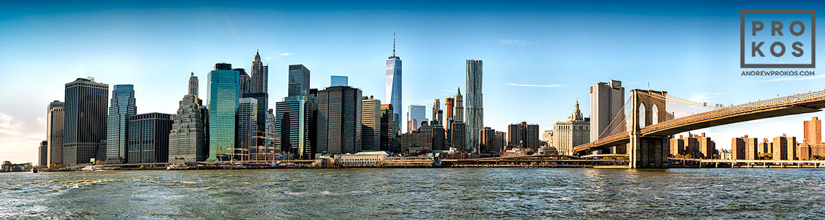 A panoramic photo of the Lower Manhattan skyline and the Brooklyn Bridge, New York City during the day. Large-scale fine art prints of this photo are available up to 150 inches wide.