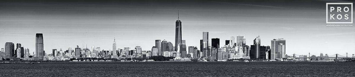 An ultra-wide panoramic skyline of New York City, the World Trade Center, the Statue of Liberty, and New York Harbor in black and white