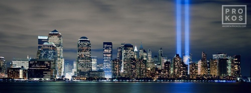 A large-format panoramic skyline of Lower Manhattan at night with the Towers of Light commemorating 9/11