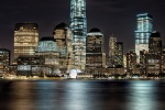 A long-exposure cityscape photo of Lower Manhattan, Hudson River, and the World Trade Center at night