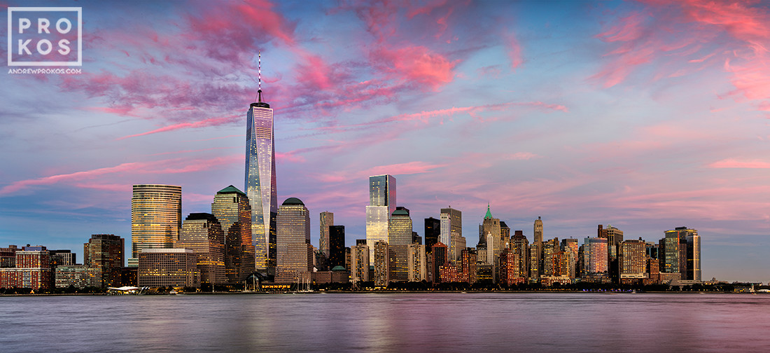 A panoramic skyline of Lower Manhattan, Hudson River, and the World Trade Center at dusk as seen from New Jersey.