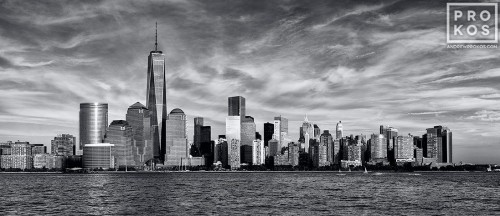 A panoramic skyline photo of Lower Manhattan, Hudson River, and the World Trade Center in black and white as seen from New Jersey