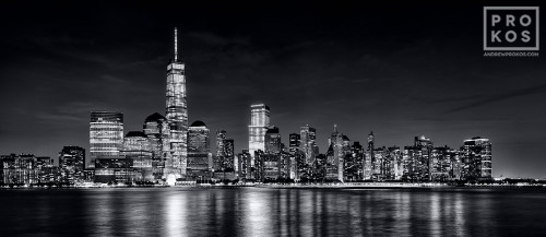 A panoramic skyline photo of Lower Manhattan, Hudson River, and the World trade Center at night in black and white as seen from New Jersey
