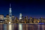 A long-exposure panoramic skyline photo of Lower Manhattan, the Hudson River, and the World trade Center at night as seen from New Jersey.
